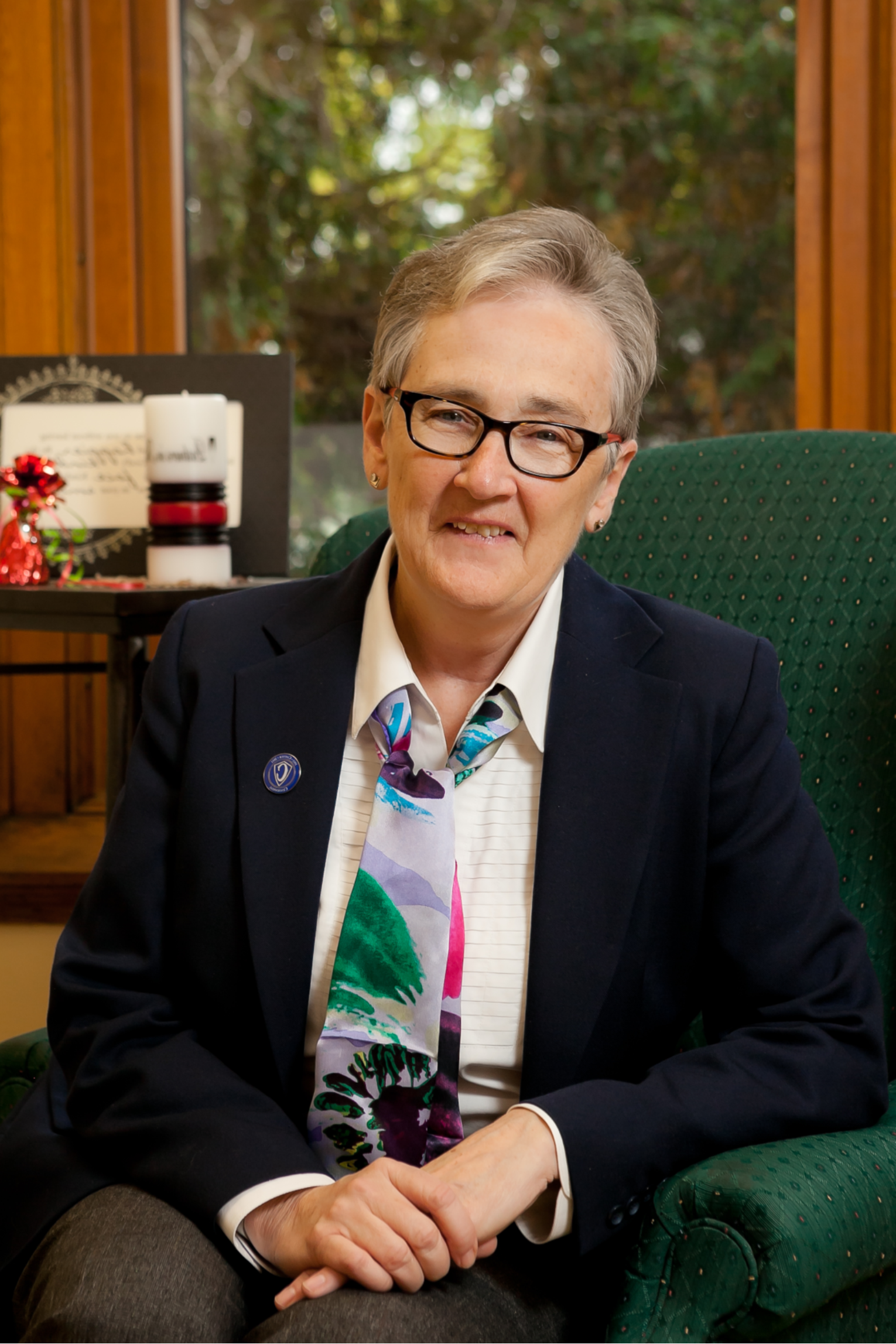 Image of Sister Judith Schaefer, OP, PhD, sitting in a green chair in her office. She is wearing glasses, a navy blue blazer, white shirt, and a silk scarf with multi-colored flowers.